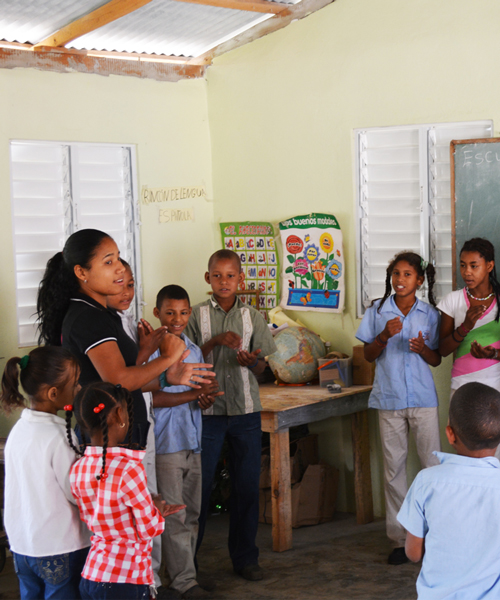 Teacher and students in the first primary school built in Hondo Valle (school built by GoldQuest)